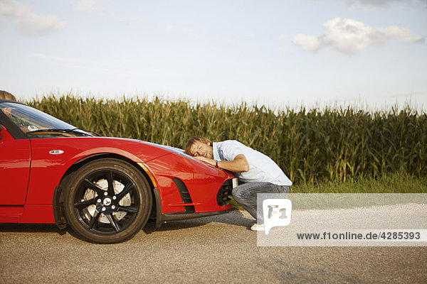 Mann umarmt seinen elektrischen Sportwagen