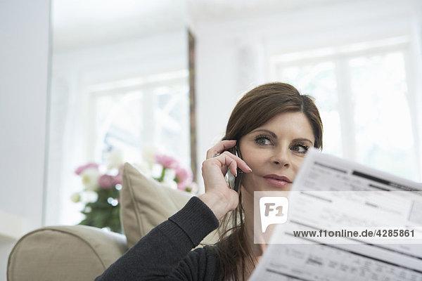 Frau am Telefon mit Dokument