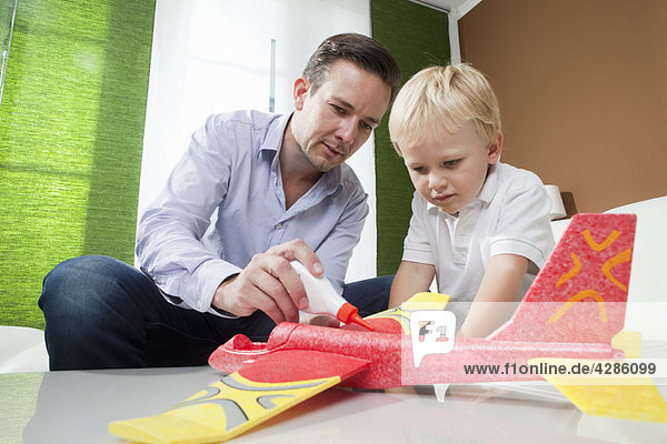 Father and son fixing toy plane