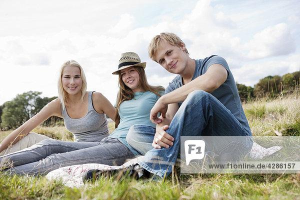Drei Jugendliche im Gras sitzend