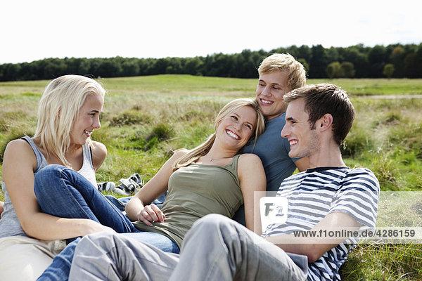 Vier Jugendliche im Gras sitzend