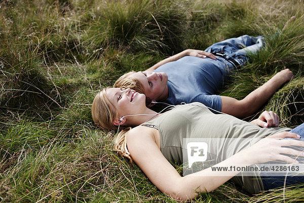 Junges Paar im Gras liegend