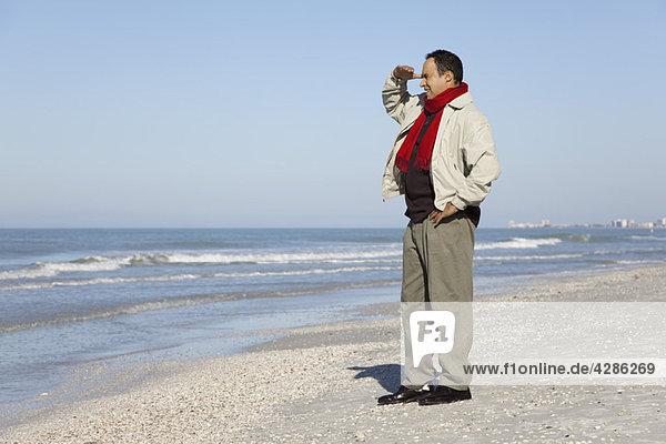 Mann am Strand stehend mit Blick auf die Aussicht
