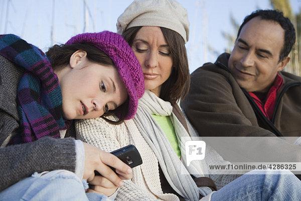 Teenager-Mädchen sitzt mit Eltern im Freien  SMS mit ihrem Handy
