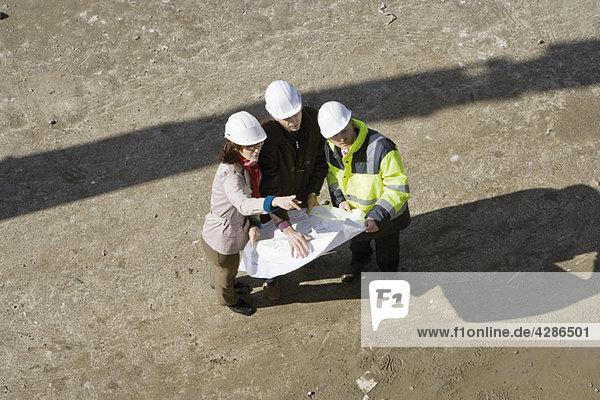 Bauunternehmer und Geschäftsleute diskutieren Blaupause  hohe Blickwinkel