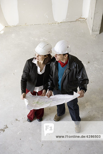 Architect and building contractor discussing blueprint