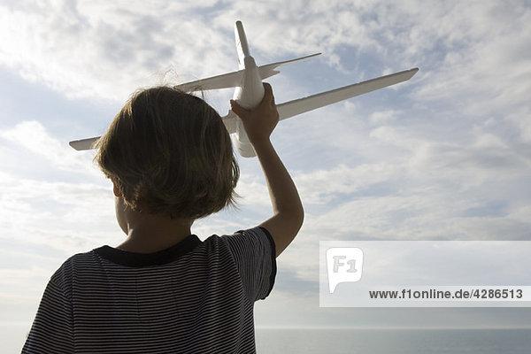 Junge spielt mit Spielzeugflugzeug  Rückansicht