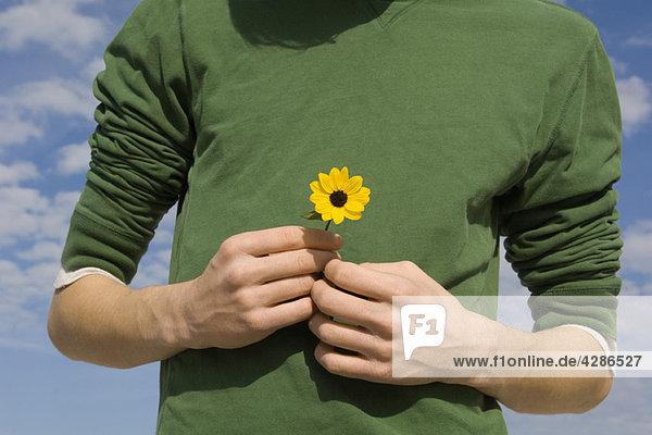 Junger Mann mit Blume