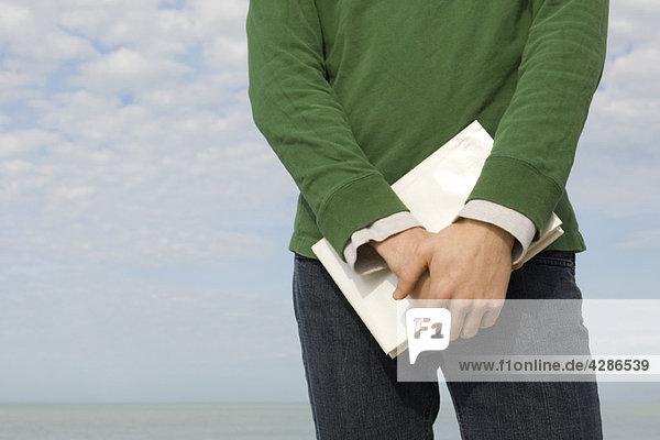Mann am Strand stehend mit Buch in Händen  beschnitten