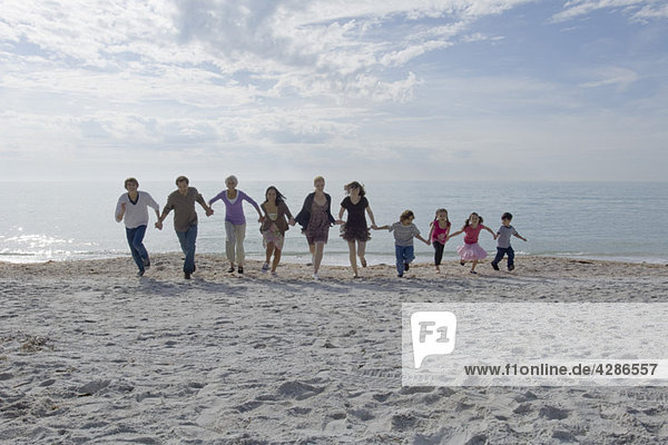 Group of people holding hands and running together on beach