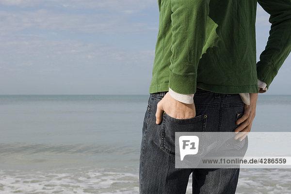 Junger Mann am Strand stehend  mit Blick auf den Strand  abgeschnitten