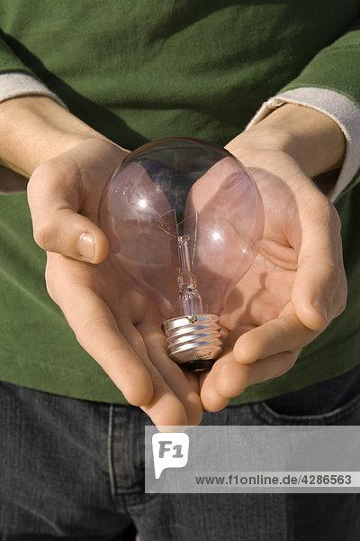 Person  die die Glühbirne in den Händen hält