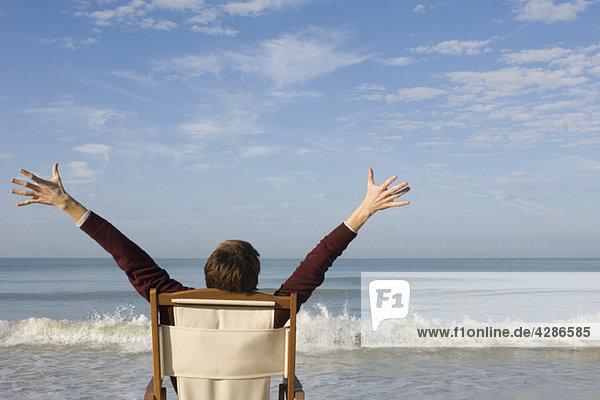Junger Mann im Stuhl am Strand mit erhobenen Armen  Rückansicht