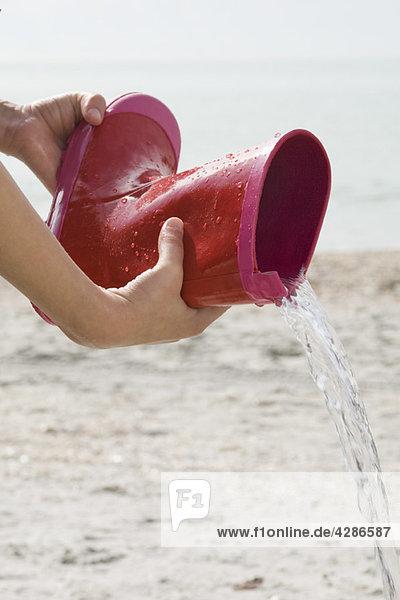 Ausgießen von Wasser aus dem Gummistiefel