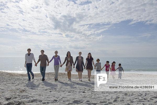 Gruppe von Menschen  die sich an den Händen halten und gemeinsam am Strand spazieren gehen.