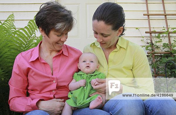 Zwei Frauen in ihre 30 s hält ihre kleine Tochter