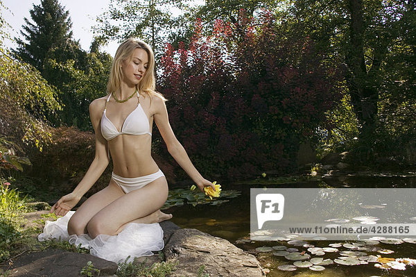Woman sitting by pond
