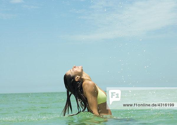 Frau im Meer stehend  Kopf zurück und Wassertropfen in der Luft nach dem Wenden von nassen Haaren