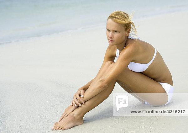 Frau im Bikini am Strand sitzend  Knie umarmend  volle Länge