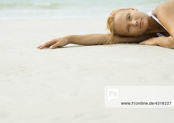 Frau am Strand liegend  mit Blick auf die Kamera