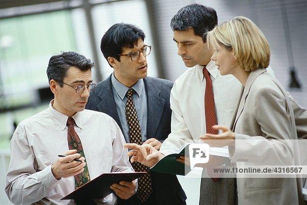 Vier Geschäftskollegen diskutieren über Dokument und Tagesordnung