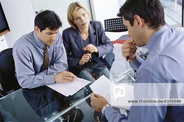 Berufspaar  das sich mit einem Geschäftsmann trifft  um Dokumente zu besprechen.