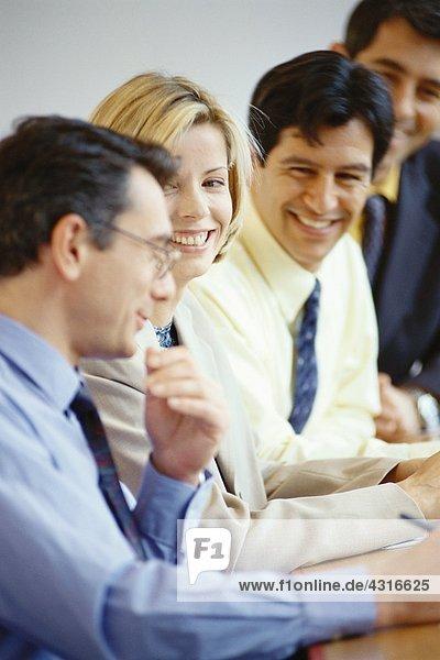 Geschäftspartner am Tisch sitzend  lachend