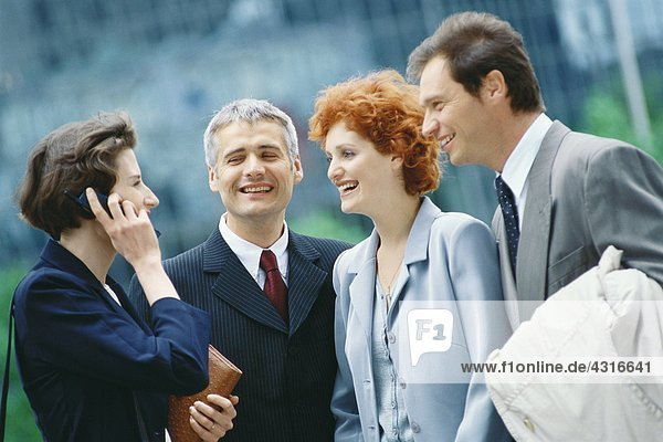 Gruppe von Geschäftsführern  eine Frau mit Handy