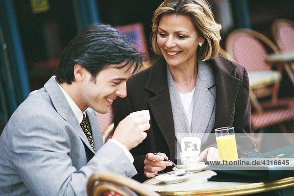 Geschäftsmann und Frau sitzen auf dem Bürgersteig.