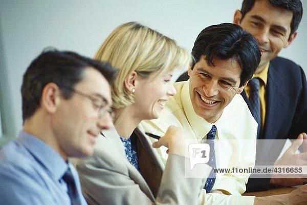 Geschäftsleute sitzen zusammen und lachen.