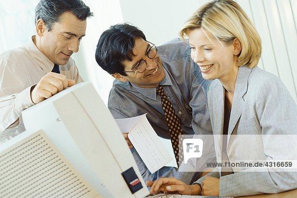 Geschäftsfreunde  die am Desktop-Computer arbeiten