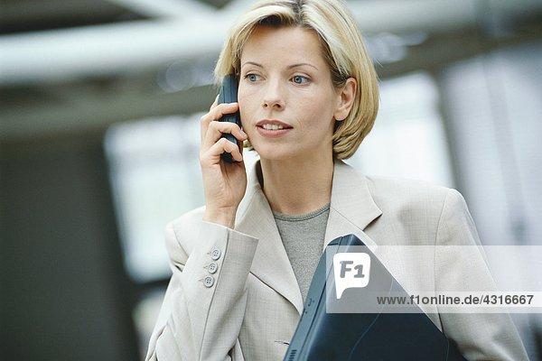 Businesswoman using phone  holding laptop