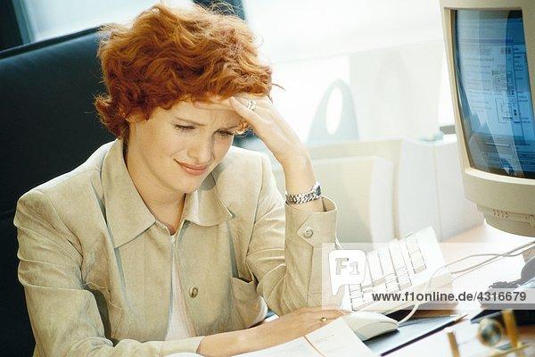 Geschäftsfrau am Schreibtisch sitzend  Kopf haltend