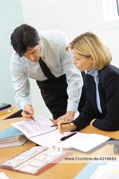 Geschäftskollegen  Mann lehnt sich über die Schulter der Frau  zeigt auf Dokumente