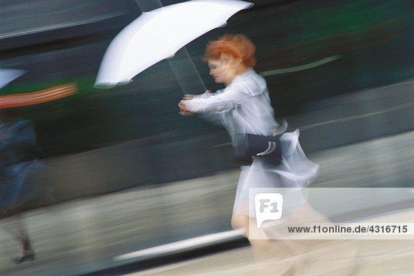 Geschäftsfrau beeilt sich mit Regenschirm