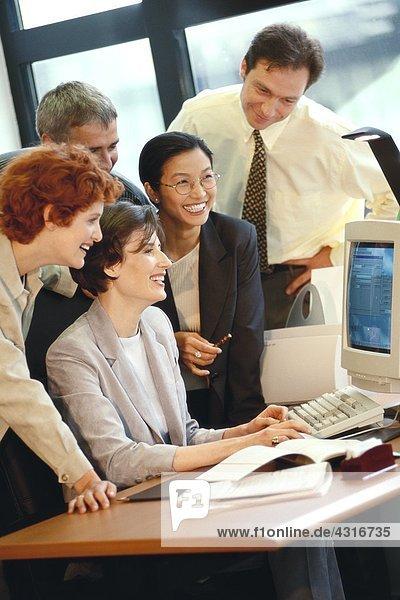 Gruppe von Geschäftsleuten  die gemeinsam am Schreibtisch arbeiten