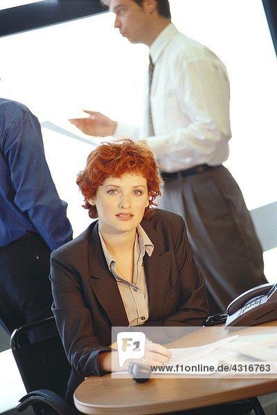 Geschäftsfrau am Tisch  Kollegen im Hintergrund