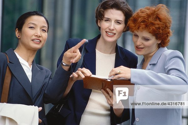 Drei Geschäftsfrauen  die sich die Tagesordnung ansehen  eine zeigt aus dem Rahmen.