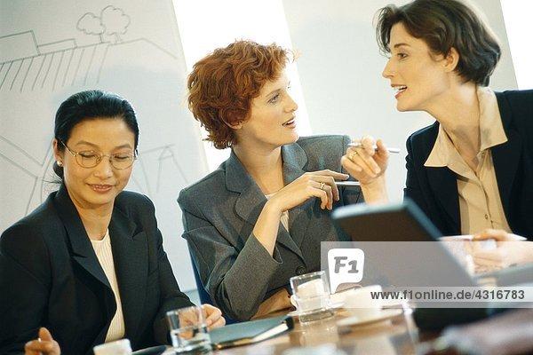 Drei Geschäftsfrau am Tisch sitzend mit Besprechung