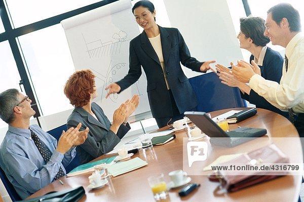 Geschäftstreffen  Frau steht  während Kollegen klatschen