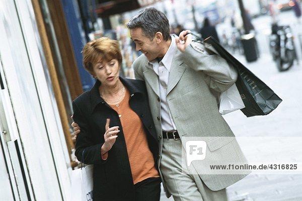 Reife Paare  die auf dem Bürgersteig der Stadt spazieren gehen