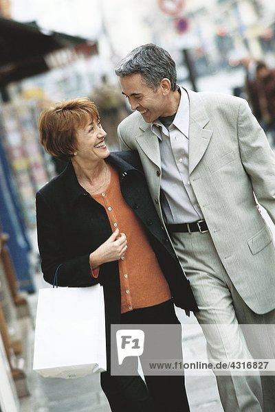 Ein reifes Paar  das auf dem Bürgersteig geht und sich gegenseitig anlächelt.