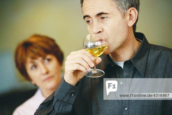 Senior Mann trinkt ein Glas Wein  Seniorin schaut ihn im Hintergrund an.