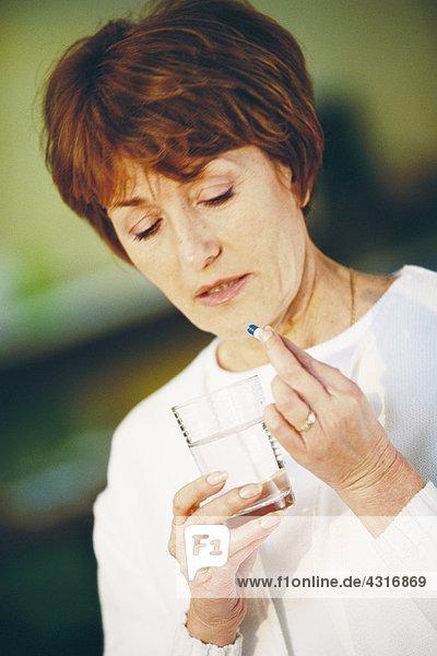 Seniorin nimmt Pille  hält ein Glas Wasser.