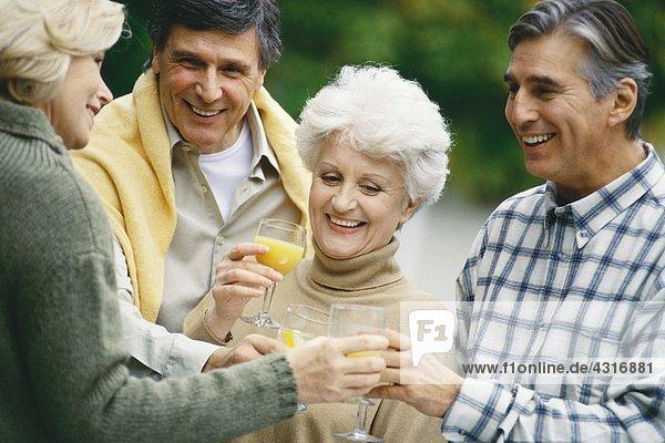 Zwei ältere Paare  die Orangensaft trinken und reden.