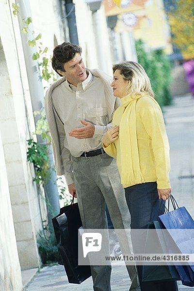 Ein reifes Paar  das auf dem Bürgersteig steht  Einkaufstaschen hält und redet.
