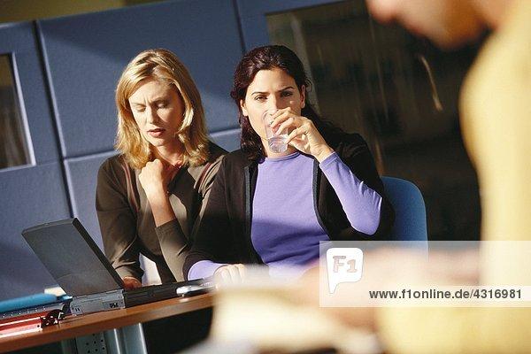 Zwei weibliche Büroangestellte mit Laptop  ein Trinkglas Wasser