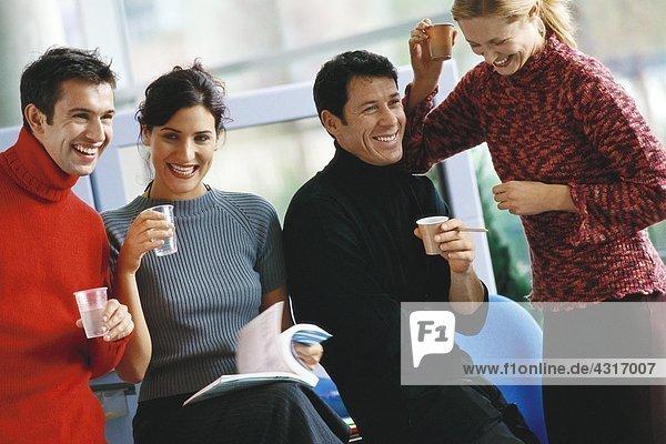 Vier Kollegen  die Tassen Kaffee und Wasser halten  lachend