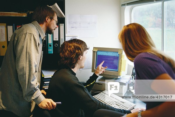 Colleagues working at computer together