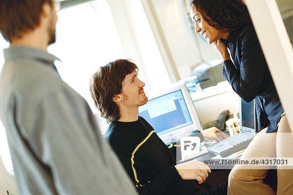 Kollegen im Büro  Frau auf Schreibtischkante sitzend  dem Mann zugewandt